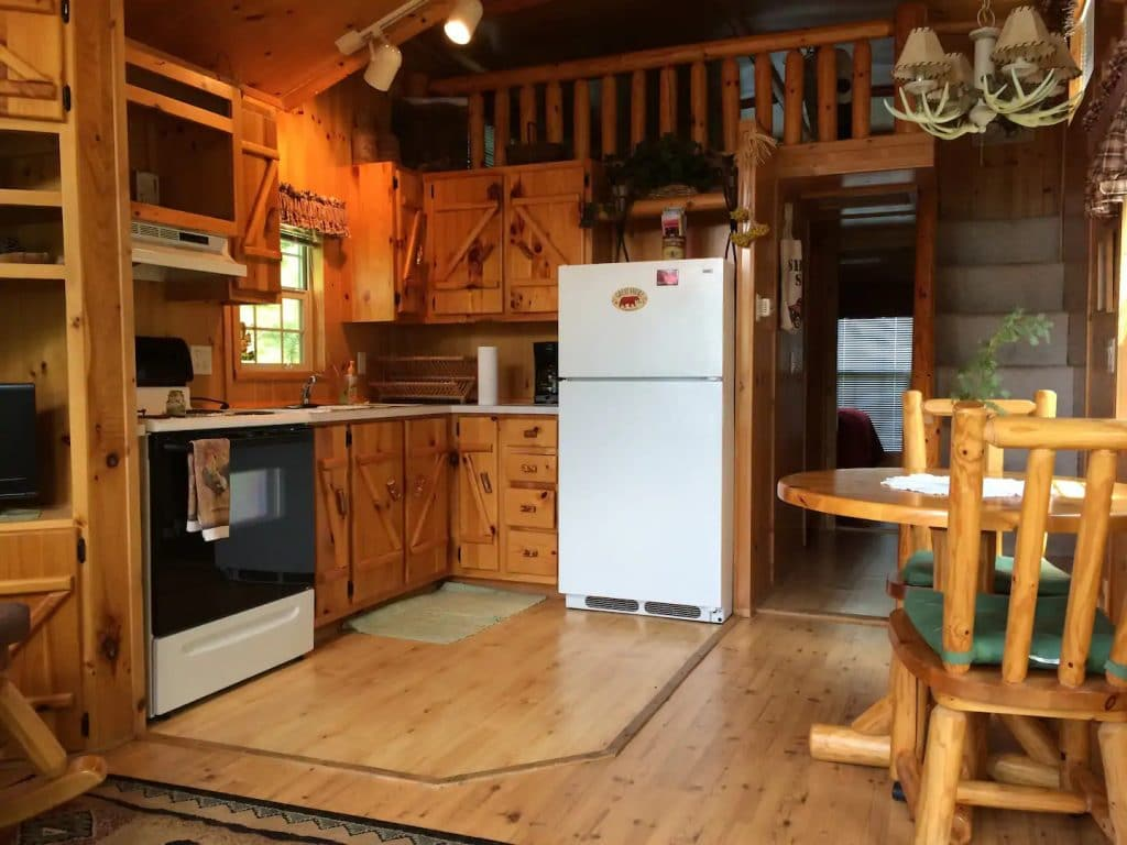 Kitchen with full sized white refrigerator in tiny cabin