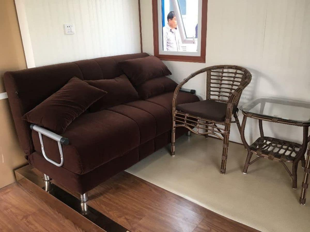 Dark brown sofa next to metal chair on platform