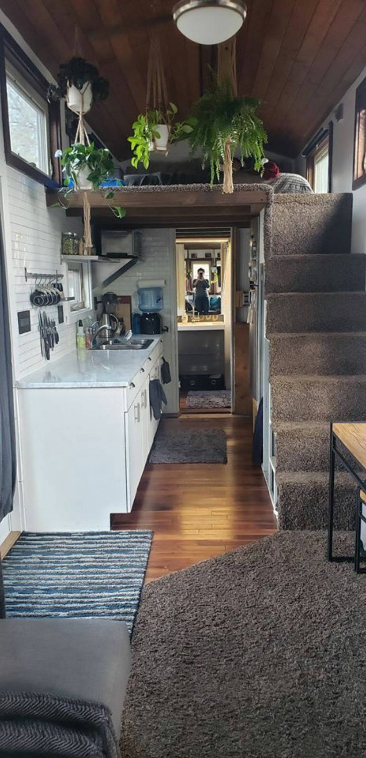 Tiny house view of kitchen with white counters