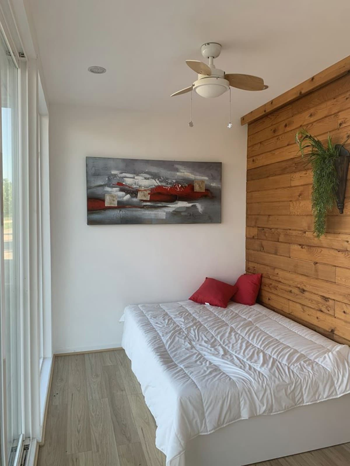 Bed against wood paneled wall