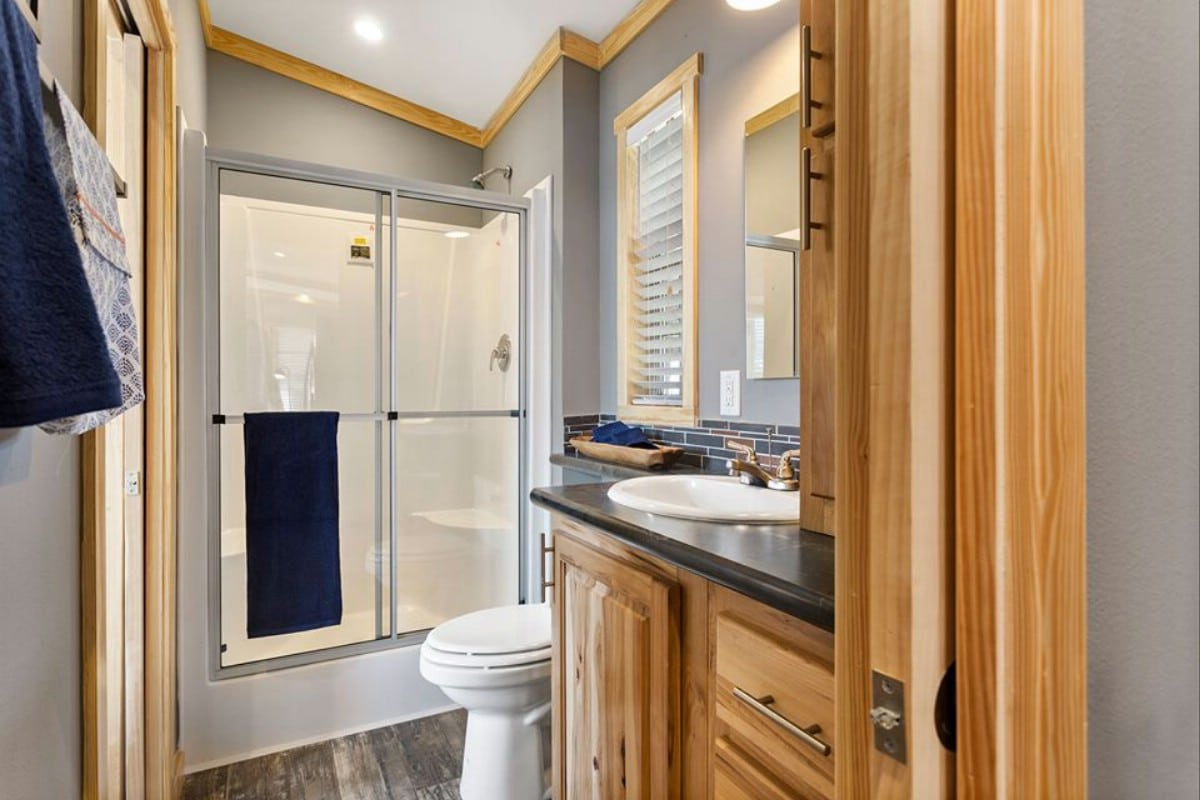Glass shower with blonde wood trim