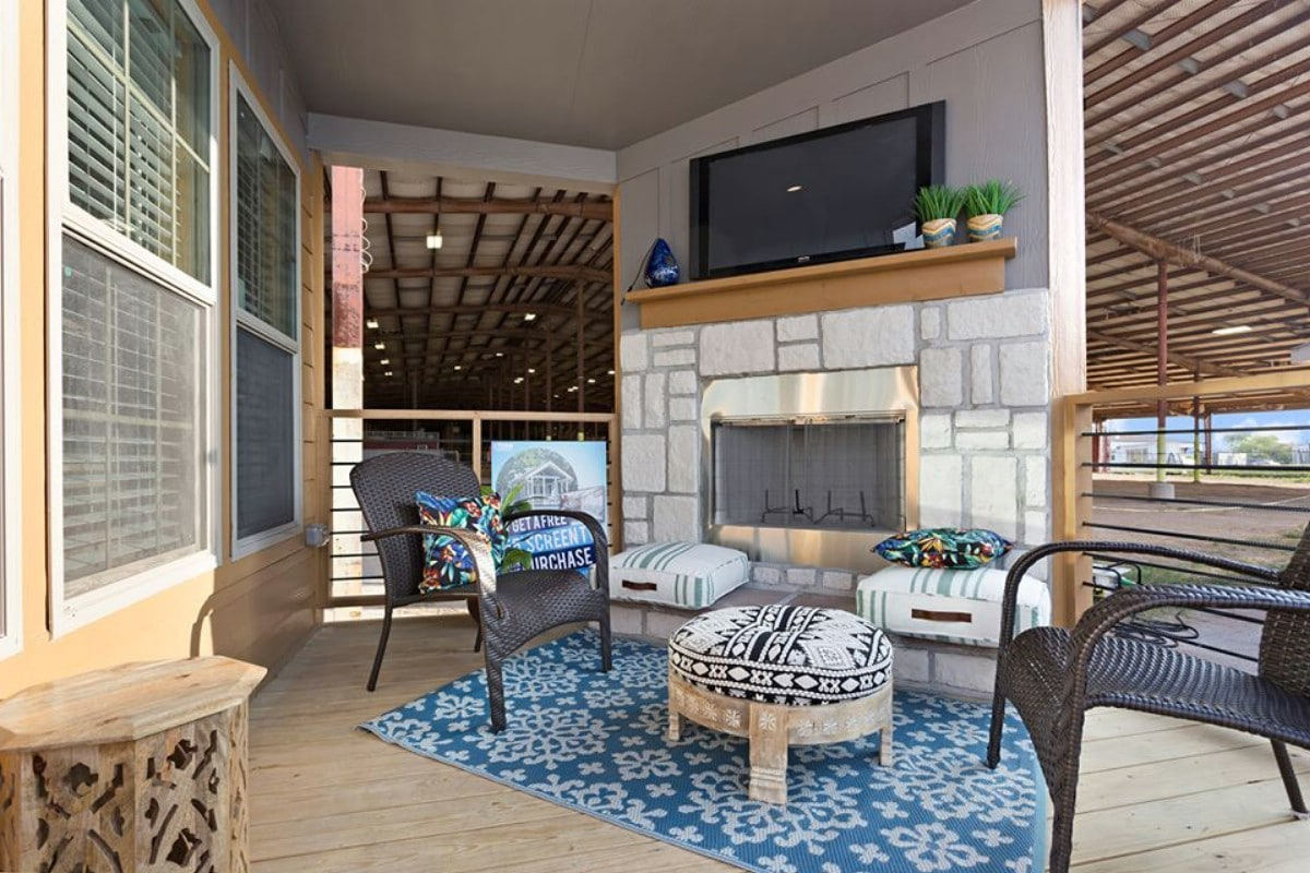 Stone fireplace and TV on porch