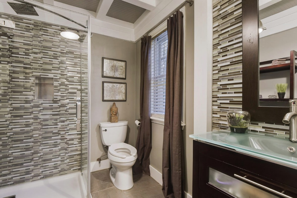 Bathroom with tile wall and glass counter
