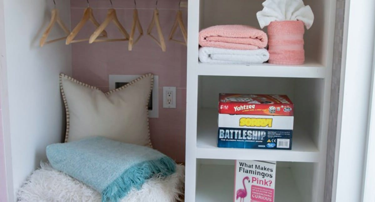 Small white closet with pillows and games