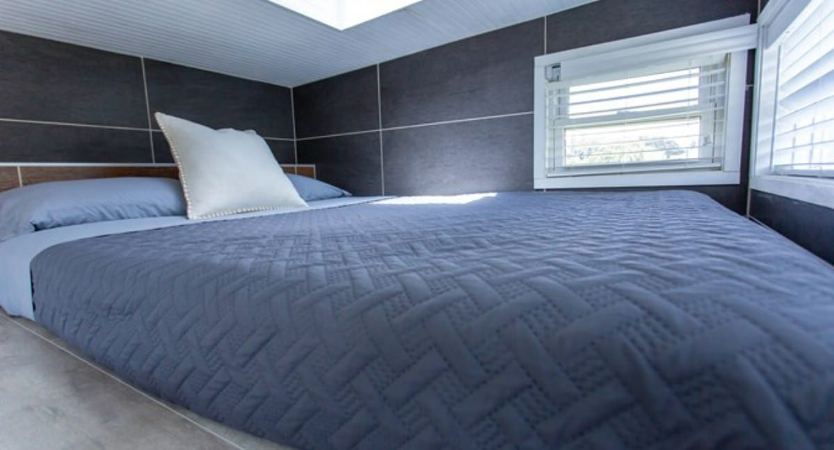 Bed in loft bedroom with blue spread