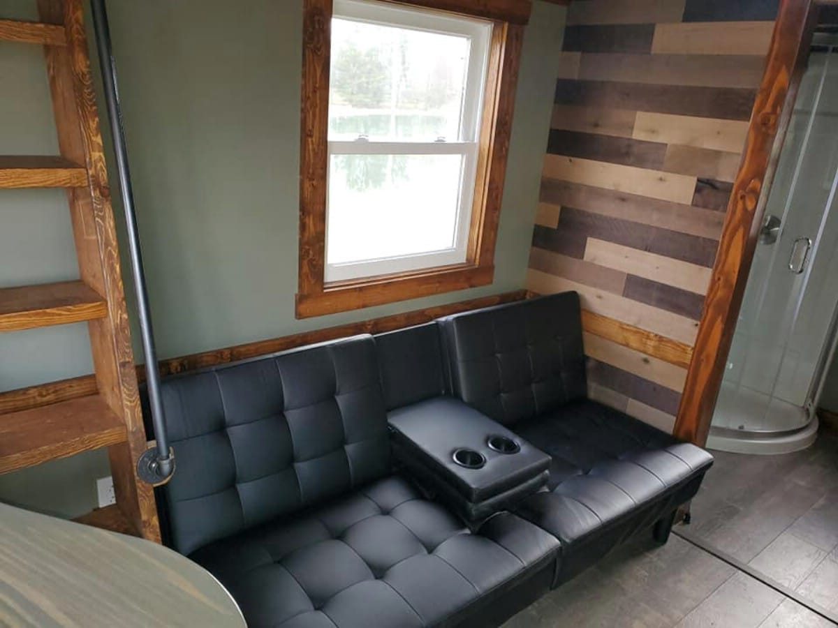 Black couch on wall of tiny home