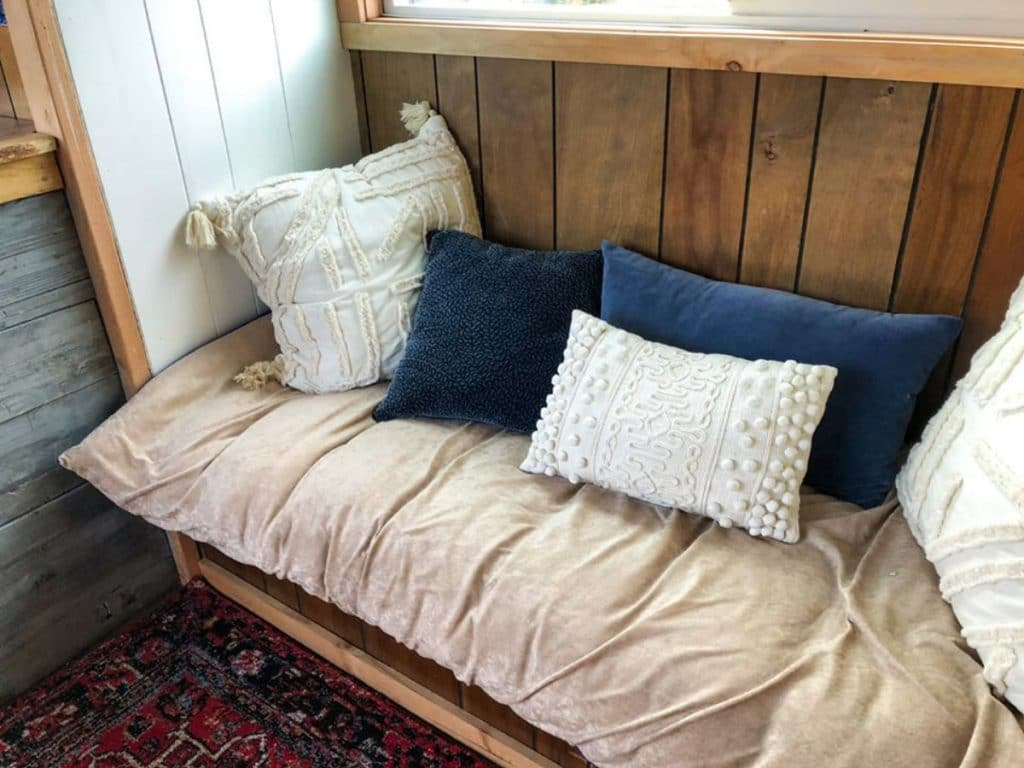 Wooden bench window seat with blue pillows