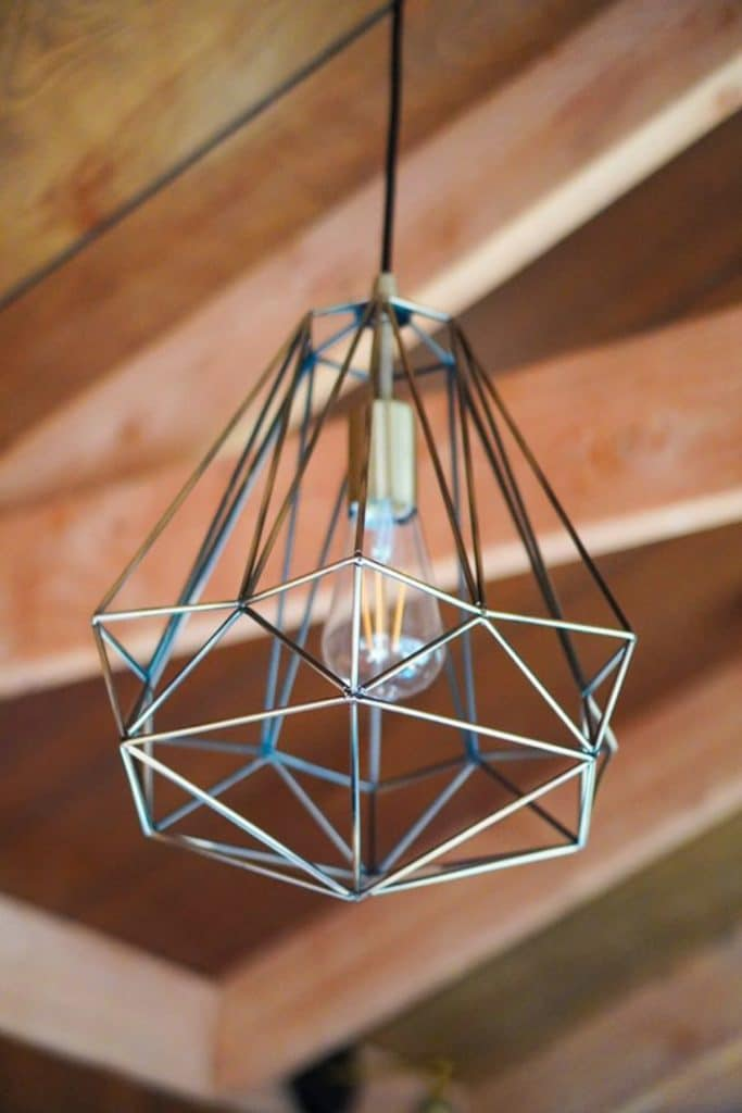 Industrial geometric light fixture hanging from ceiling