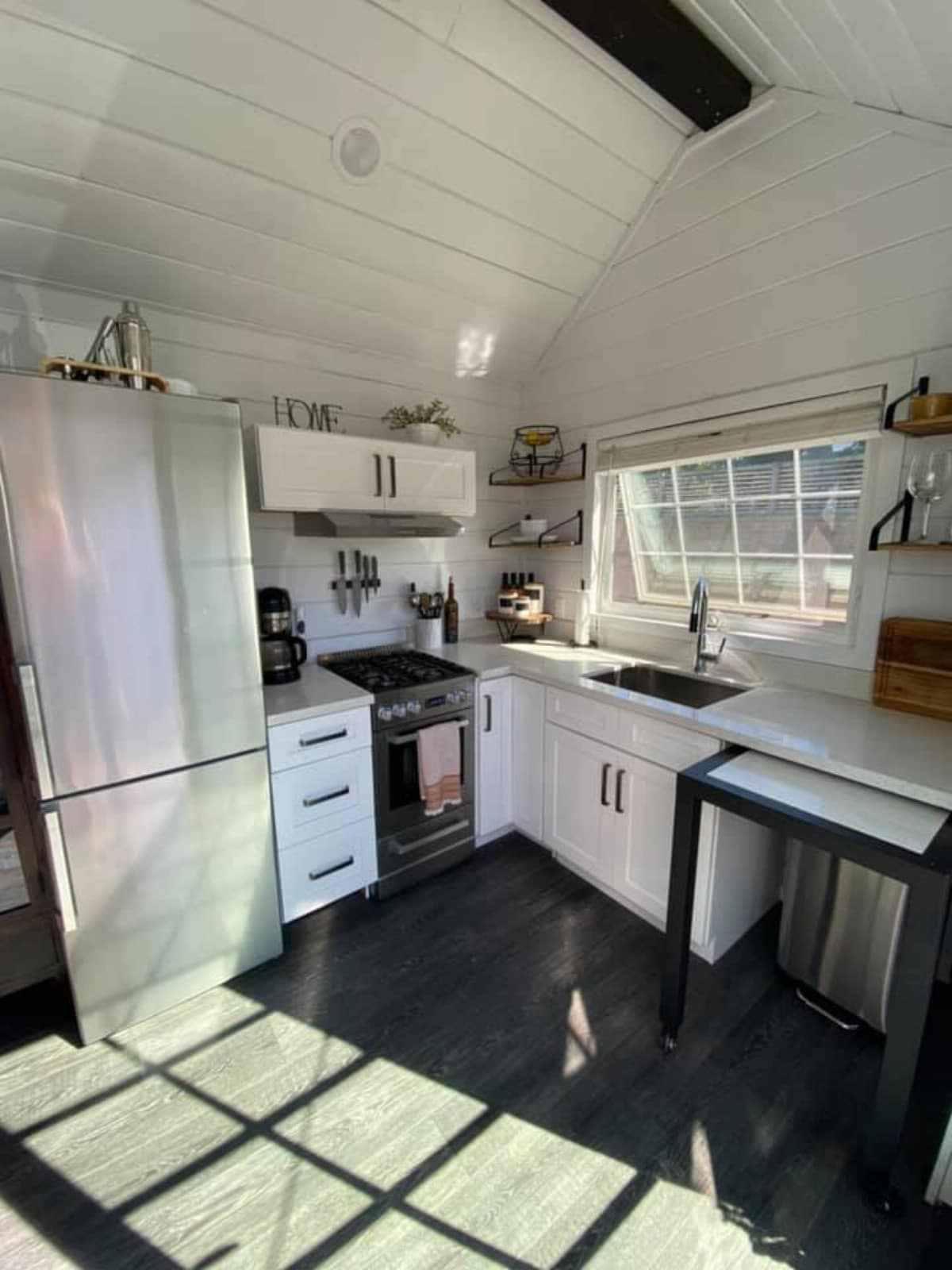 Full kitchen in white walled tiny house