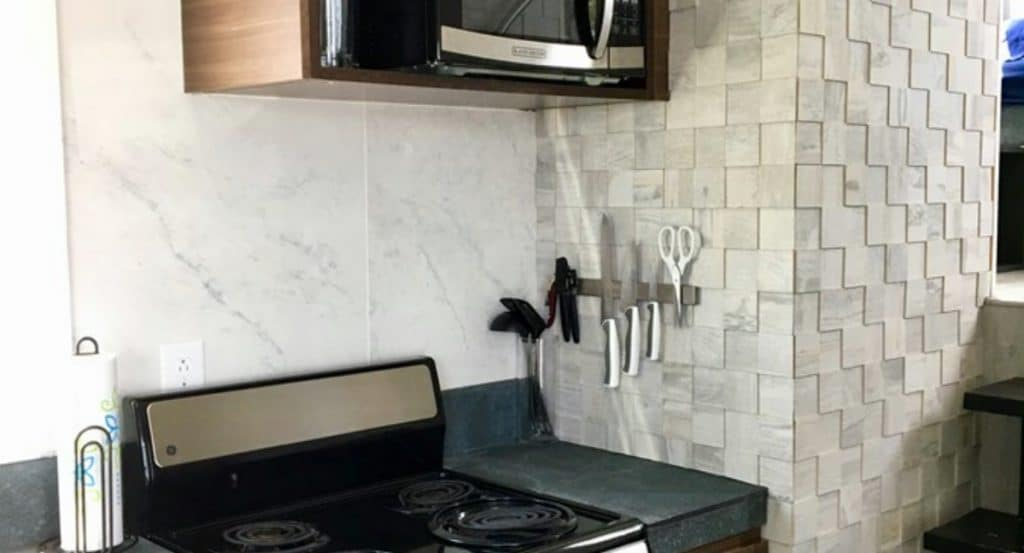 Stove with magnetic utensil strip on wall