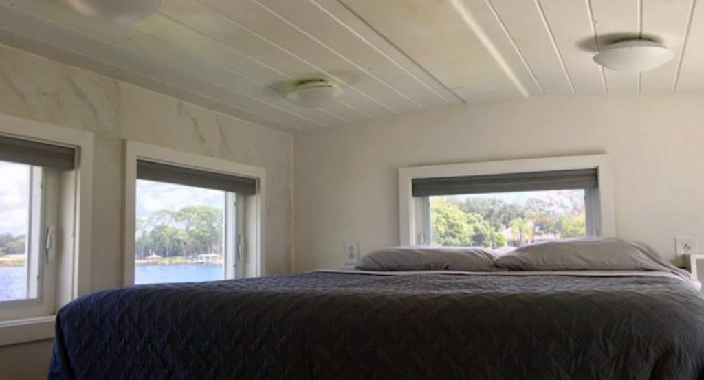 Bed in loft with multiple windows and white shiplap ceiling