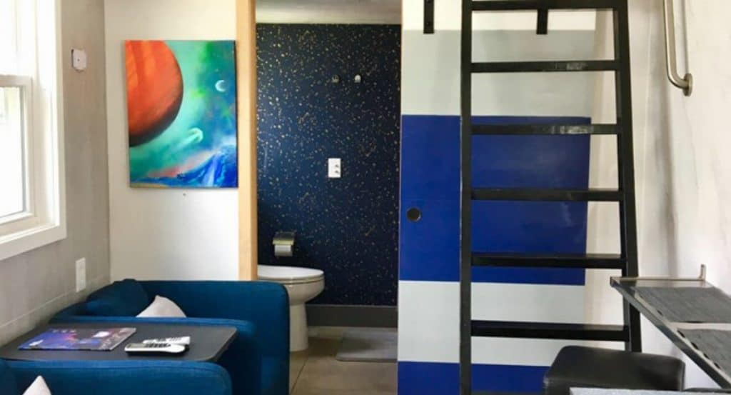 View into living area of galaxy themed tiny home with blue walls