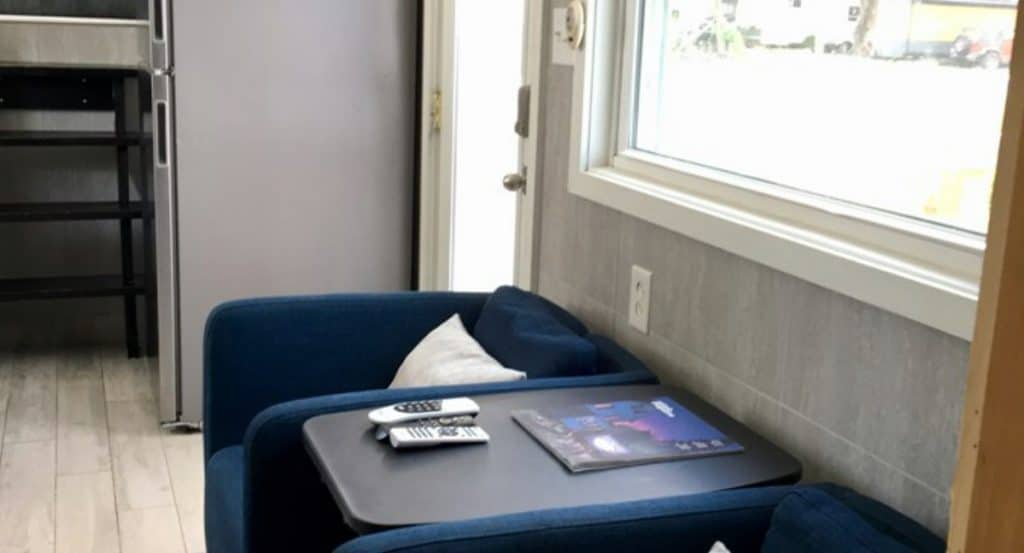 Blue chairs with black table between them under window