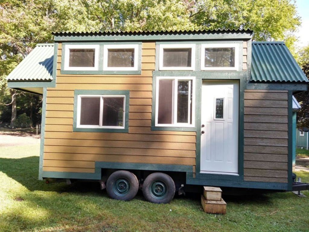 Cabin tiny home with 8 windows and white door