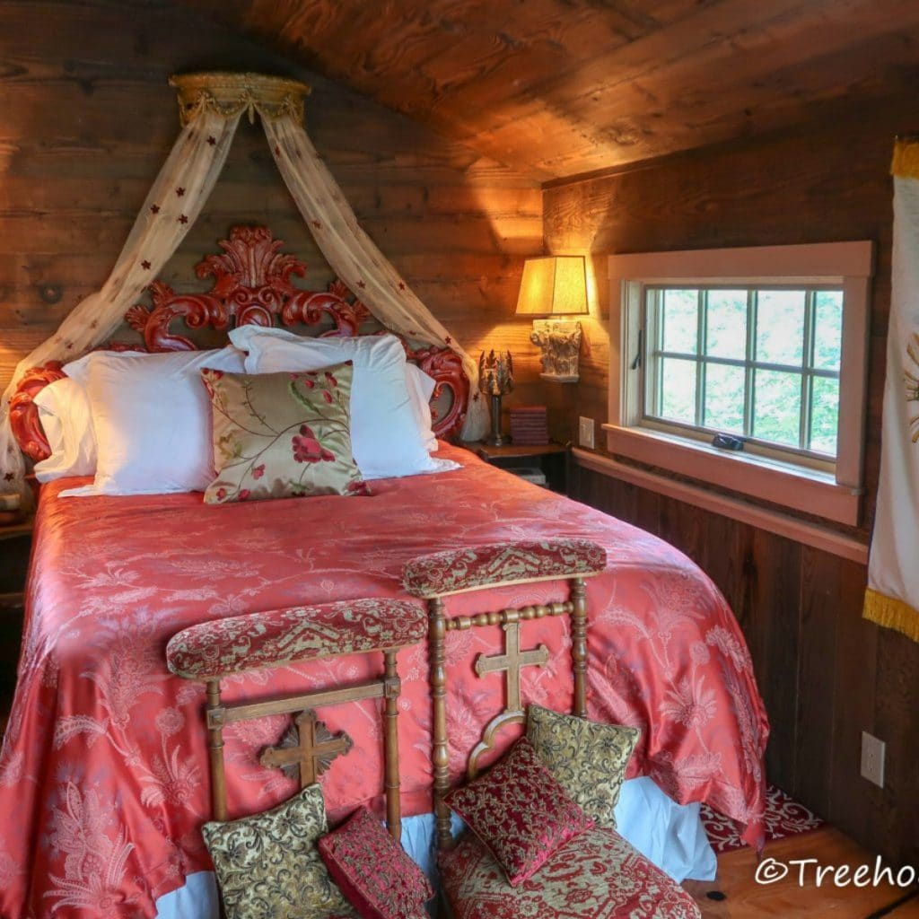 Large bed with pink bedding in Chapelle treehouse