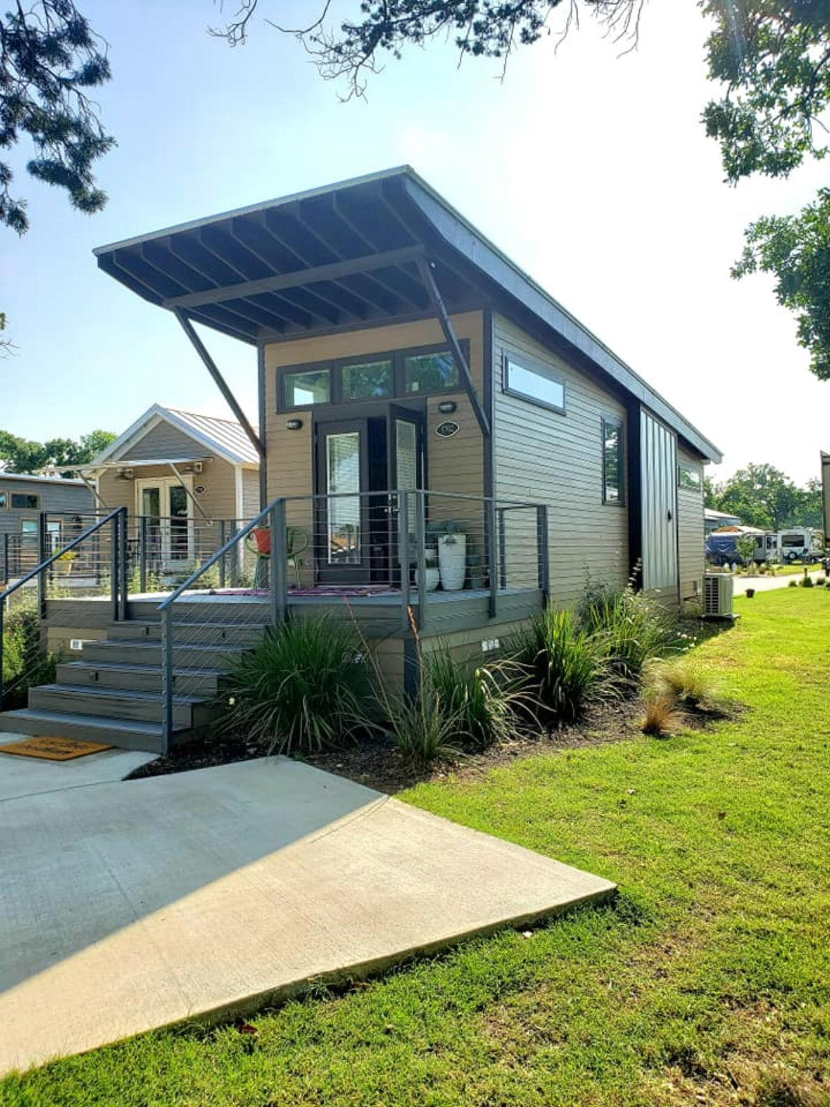 Front of tiny home with green grass and concrete walkway