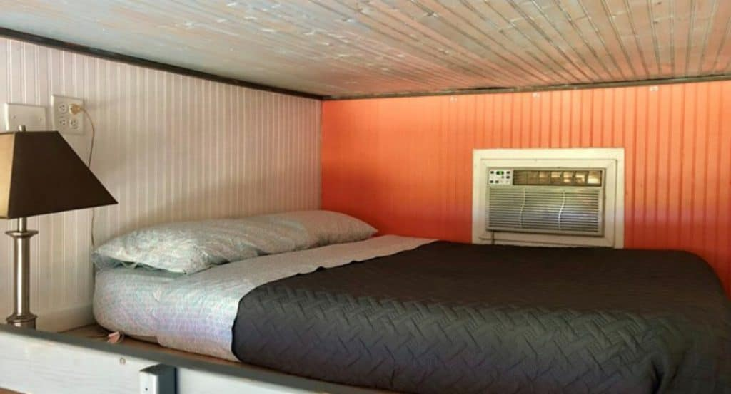 Loft bed with white ceiling and coral wall
