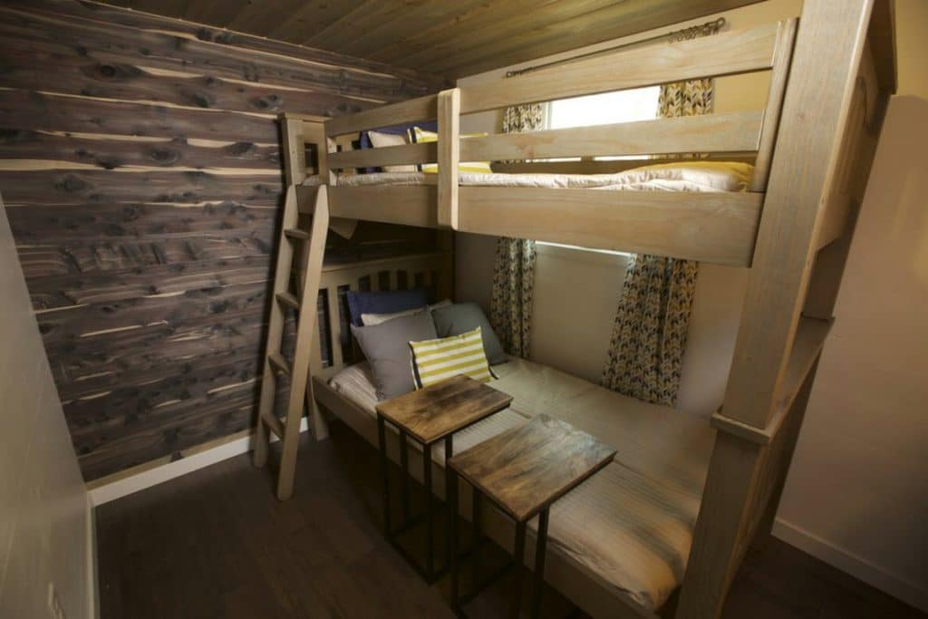 Bunk beds in kids bedroom with wood walls