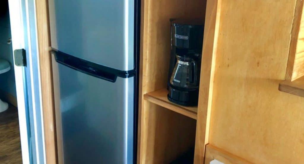 Refrigerator by wood shelf with coffee pot