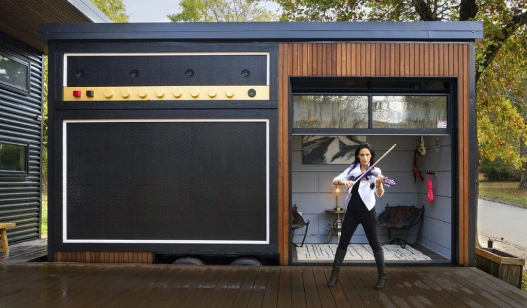 Woman playing violin outside tiny recording studio