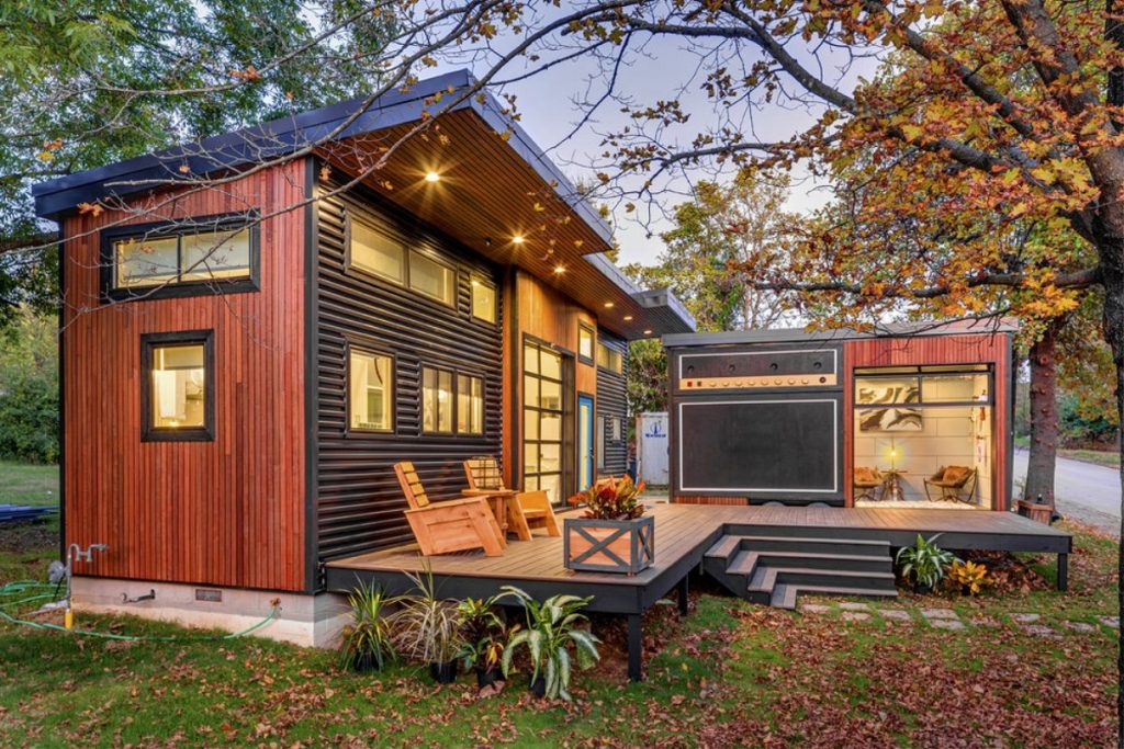 Wood siding on tiny home with lights at dusk