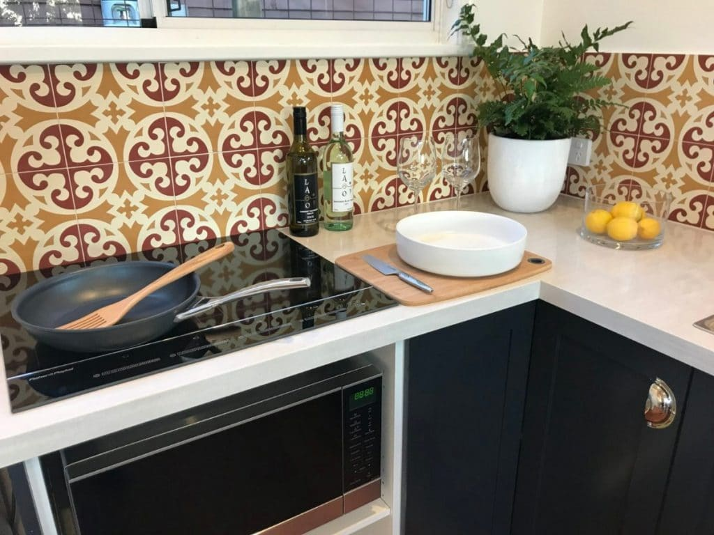 Decorative tile behind stove in tiny kitchen