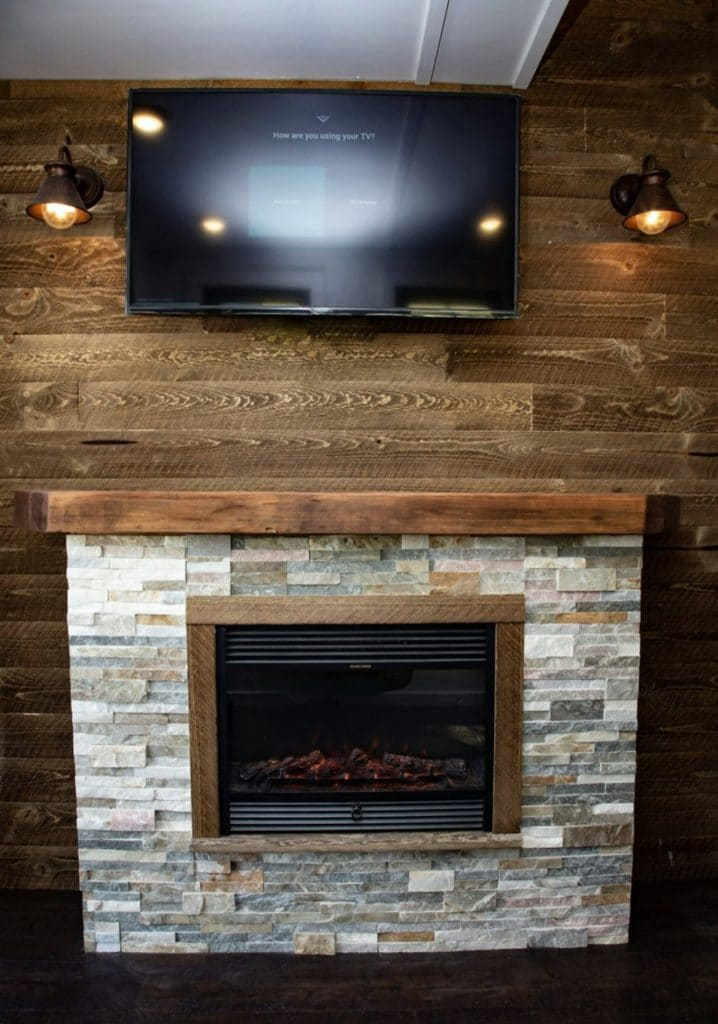 Brick fireplace against wood paneled wall