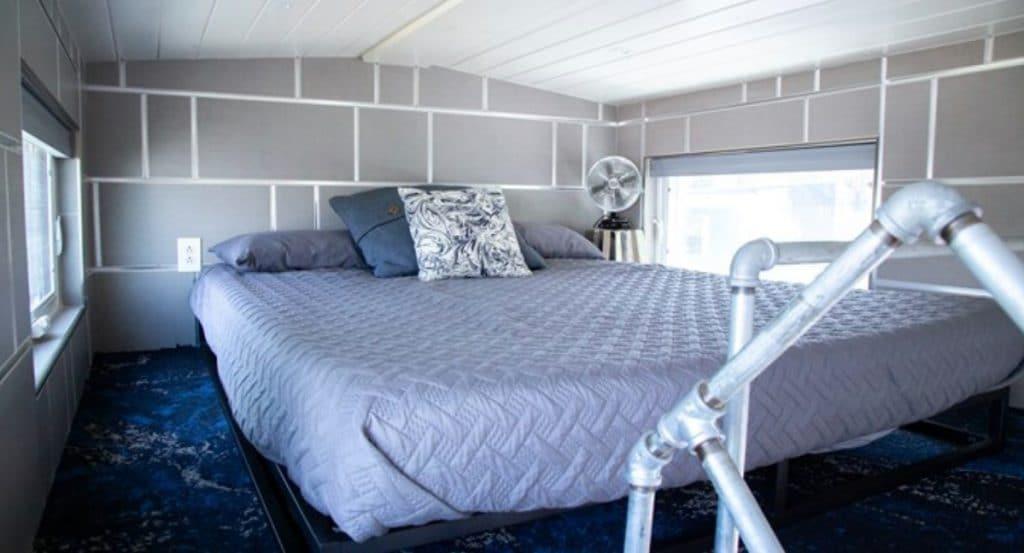 Loft bedroom with textured blue blanket