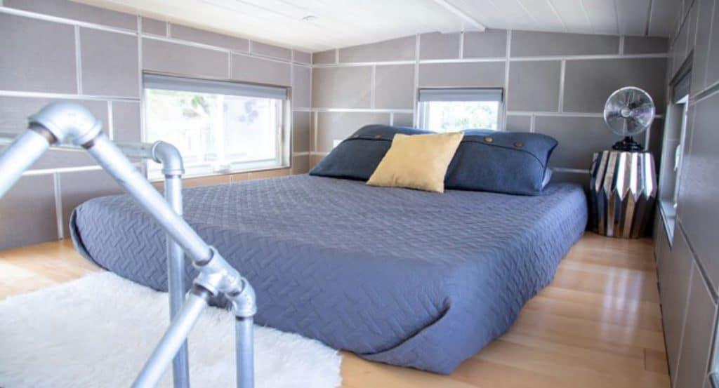Loft bedroom with blue blanket on bed