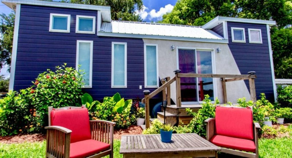Blue and white tiny home with red chairs in front