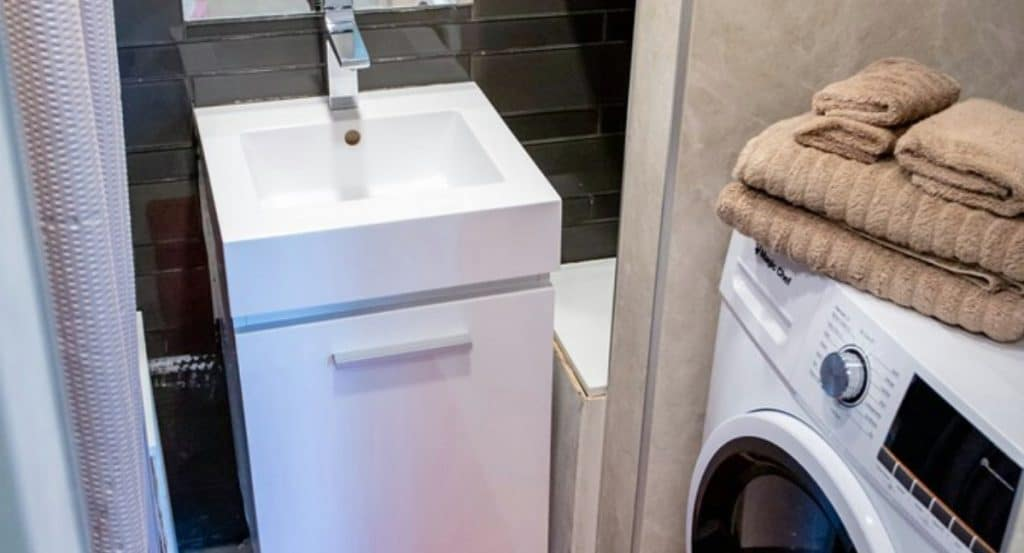 Square white bathroom sink next to washing machine