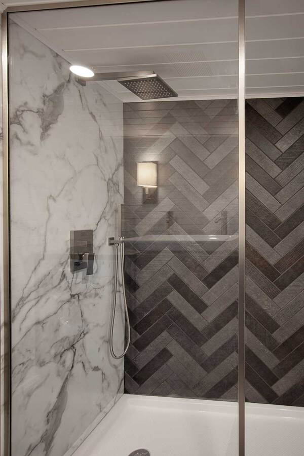 Marble tiled shower in breezeway tiny house