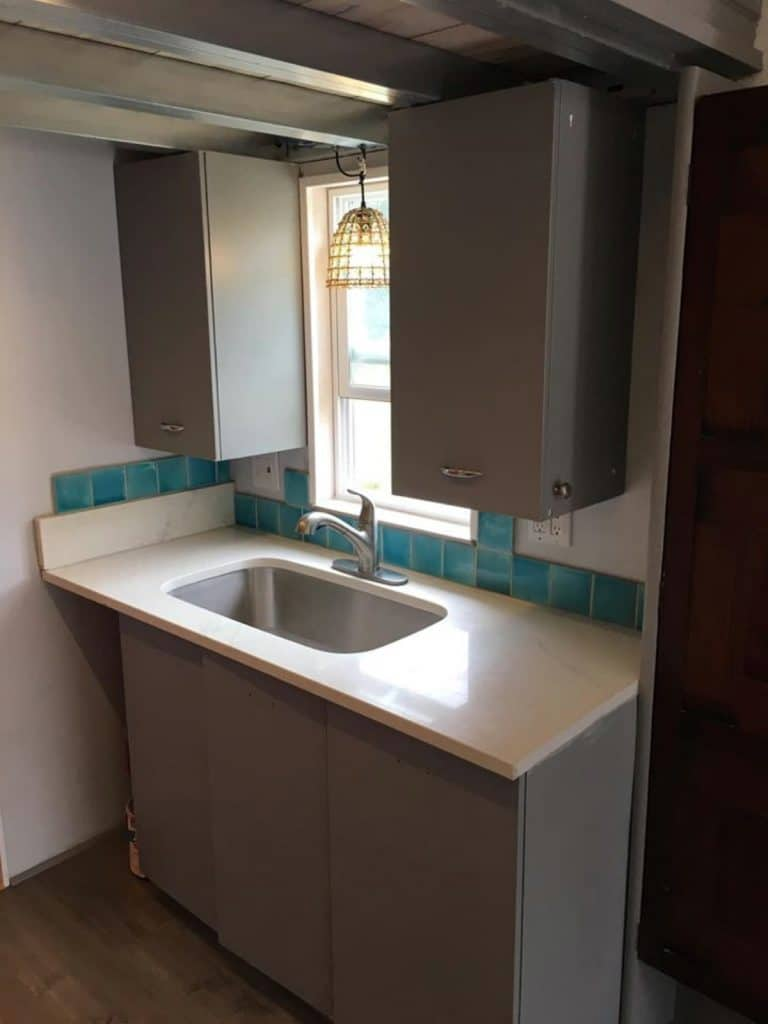 Tiny house bathroom sink with teal tiles