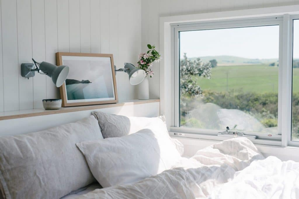 Bed with white linens by window