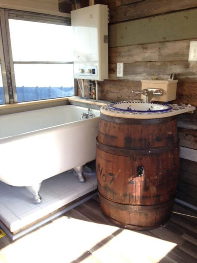 Clawfoot bathtub with rain barrel sink