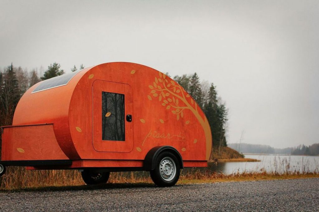 Orange teardrop camper by lake