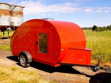 Orange teardrop camper by silo