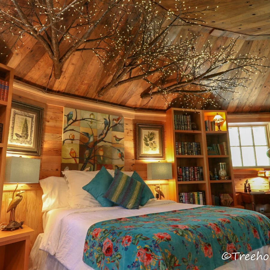 Bed with blue floral bedding and tree above