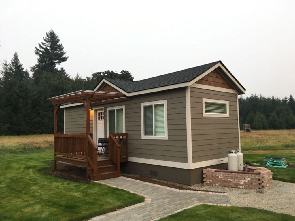 Olive green tiny house with porch