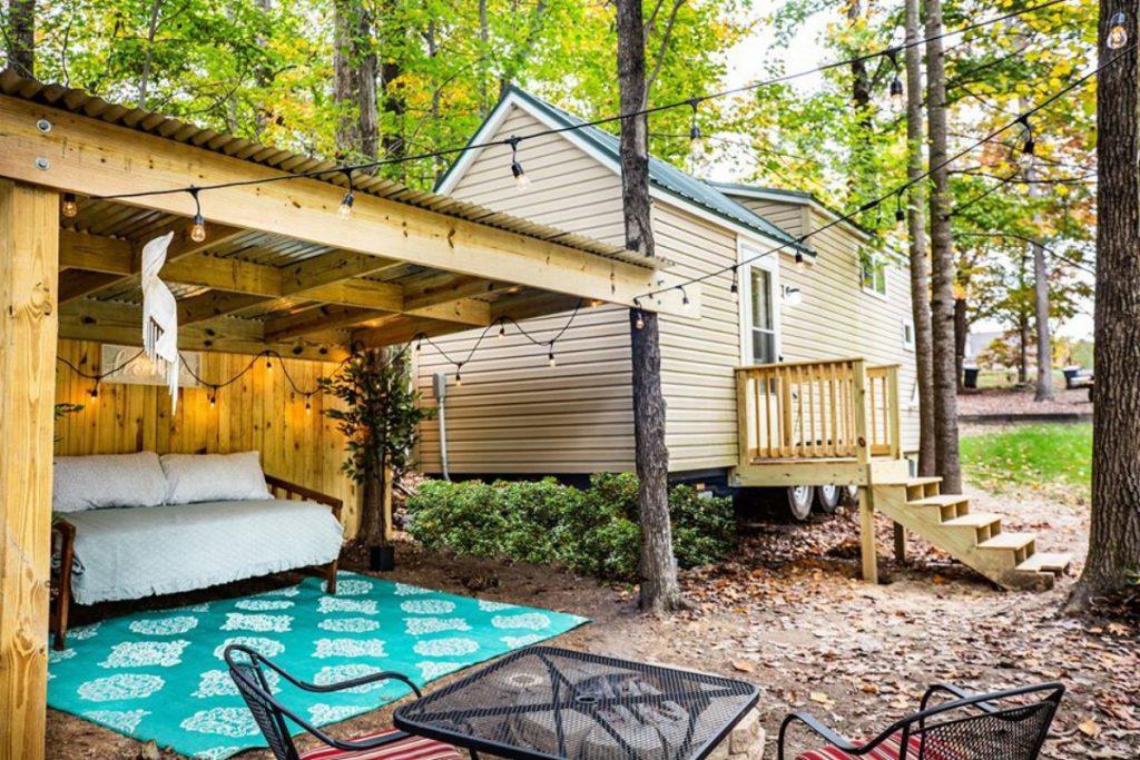 Vinyl siding tiny house with wood porch