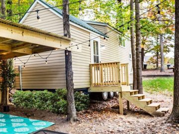 Vinyl siding tiny house with wood porch