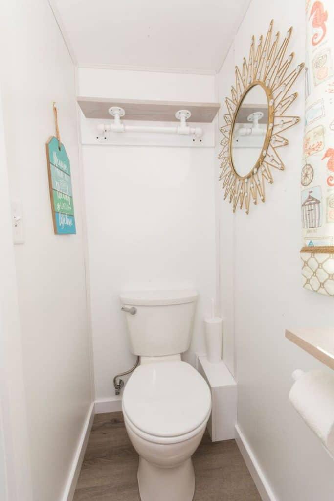 Toilet in white bathroom with sunburst decor