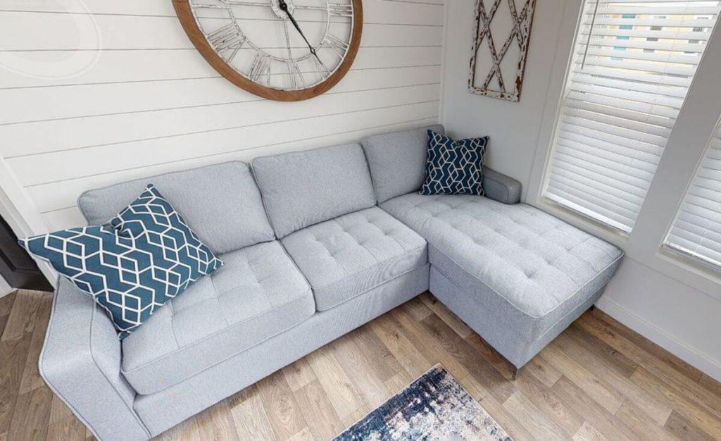 Gray sofa under large clock