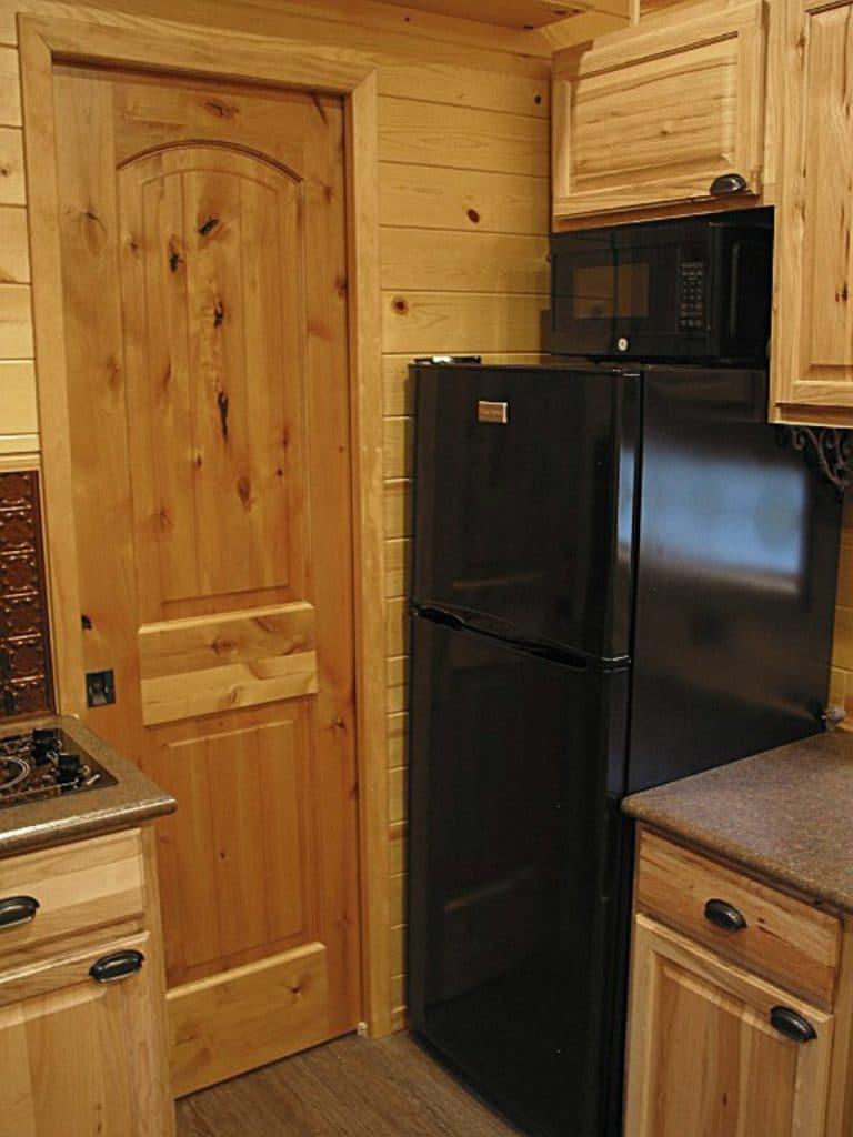 Black refrigerator by door