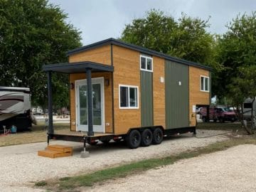 Brown and green tiny house with porch