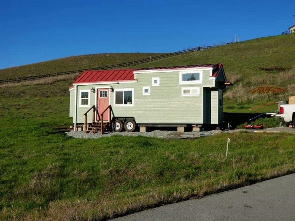 Green tiny house on hill
