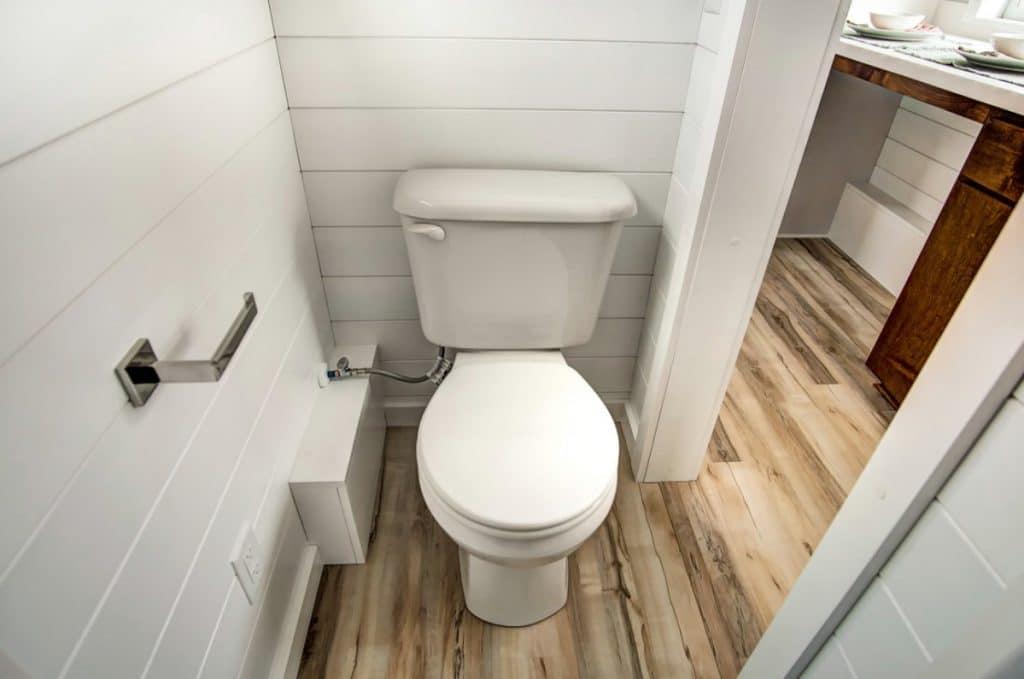 Toilet with white shiplap walls