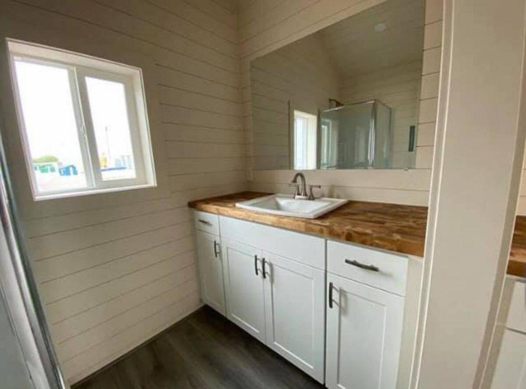 White bathroom vanity with butcher block countertop