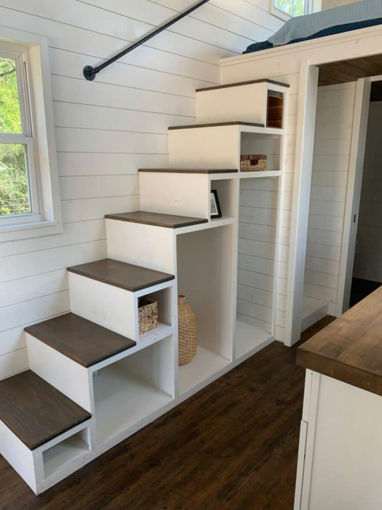 White and wood stairs with cubby underneath