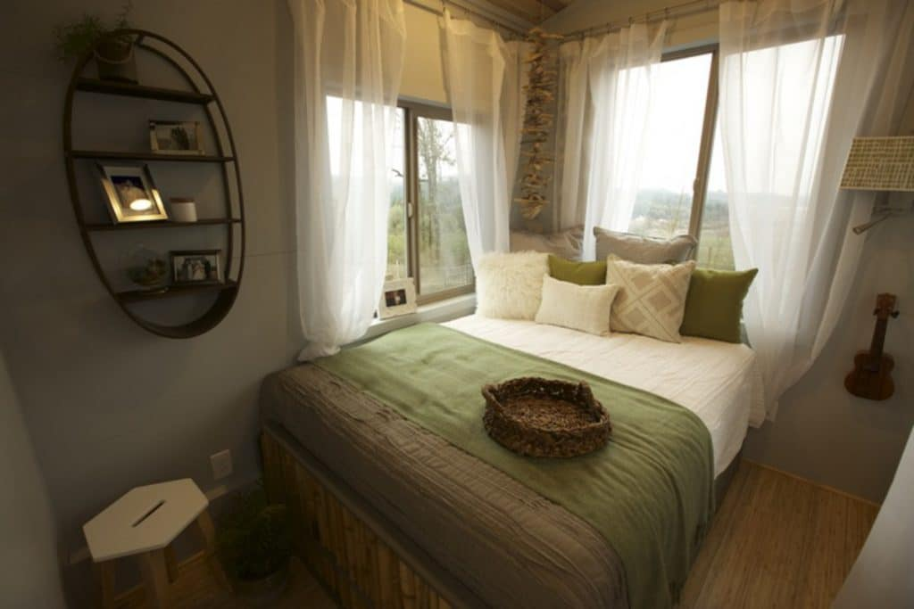 Green bedding on tiny house bed